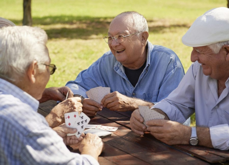 Seniors playing a card game to keep their brain active