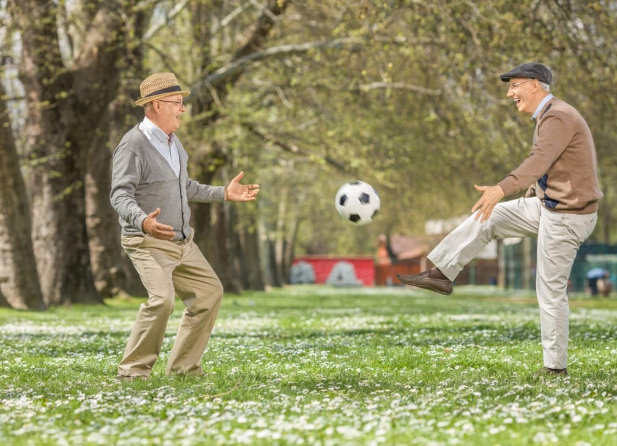 Two seniors playing soccer outdoors